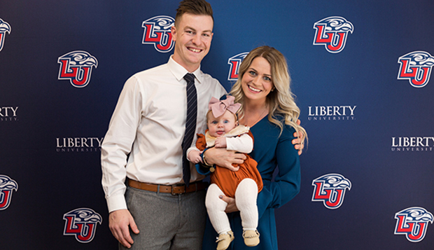 Stacey McCombe and her husband, former Flames DI men's hockey forward Andrew McCombe, hold their 4-month-old daughter, Willow, at the Dec. 8 Club Sports Hall of Fame induction ceremony. (Photo by Gabrielle Calhoun) test test test test