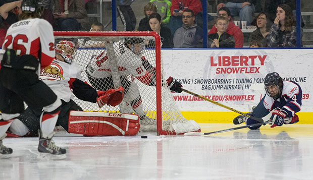 Liberty senior defenseman Steven Bellew makes a diving stab at the puck in an attempt to score a wraparound goal, but is denied by Minot State netminder Connor Beauchamp, Friday night at the LaHaye Ice Center.  test test test test