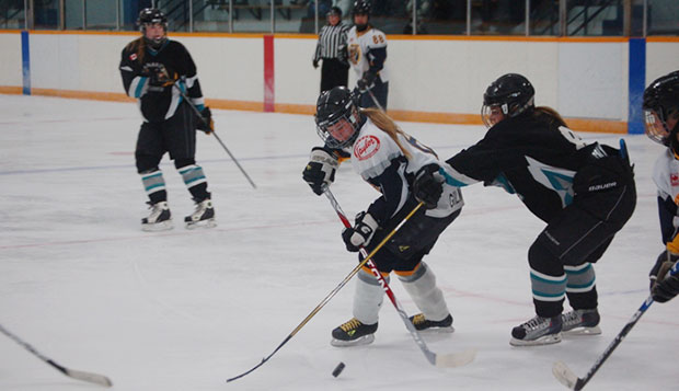 Hamilton Hawks forward Courtney Gilmour (center) handles the puck between two defenders last season. She brings finesse as well as a knack for scoring to the Lady Flames. test test test test