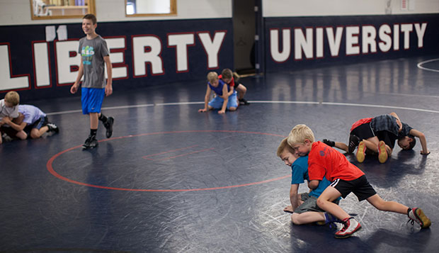 Elementary school-aged wrestlers practice under supervision from Liberty University head coach Jesse Castro and a handful of his wrestlers Tuesday in the Wiseman Wrestling Room. test test test test