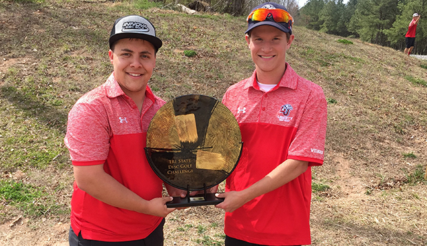 Zach Biscardi and Christian Wilborn showcase their doubles championship trophy at Saturday's Tri-State Disc Golf Challenge. test test test test