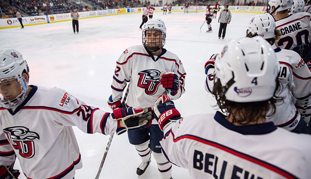 Freshman defenseman Zane Schartz is greeted on Liberty's bench by teammates including defensive linemates Kyle Crane (right), Jackson Giammona, and Steven Bellew. test test test test