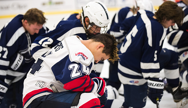 Liberty senior forward Zechariah Roberts, shown praying with Penn State players last season, is one of a few spiritual leader representatives from the Flames' ACHA Division I men's hockey team. (Photo by Leah Stauffer)  test test test test
