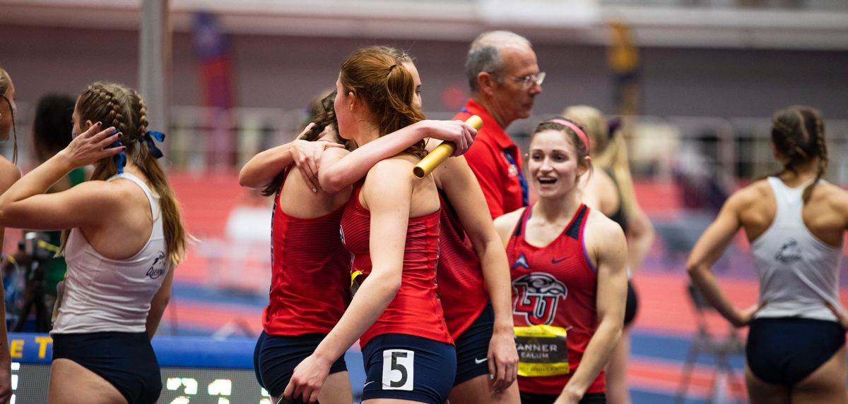 The Lady Flames celebrate their victory and school record in the women's distance medley relay.